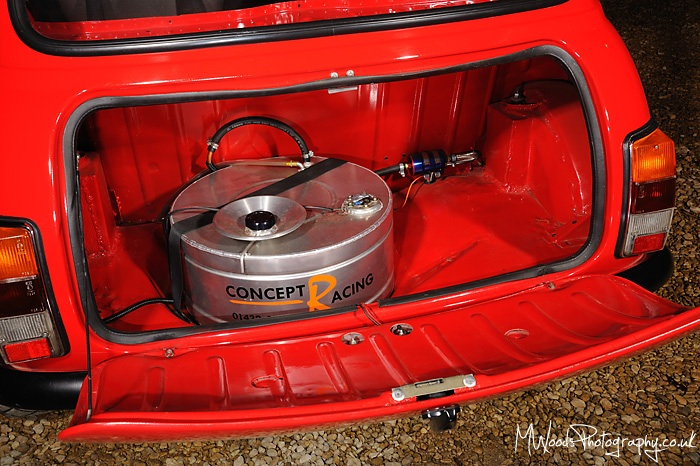 Round mini fuel tank fitted in spare wheel well.